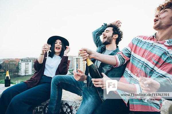 Gruppe von Freunden genießt Dachparty  junger Mann öffnet Flasche Champagner