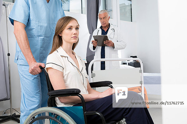 Doctor in hospital pushing woman in wheelchair
