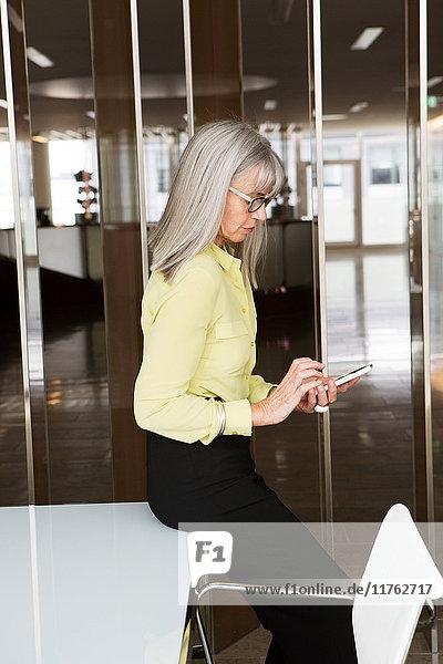 Geschäftsfrau sitzt am Schreibtisch und benutzt ein Mobiltelefon
