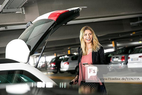 Junge Frau wartet am offenen Kofferraum mit Smartphone auf dem Flughafen-Parkplatz