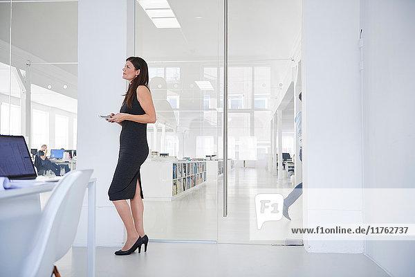 Geschäftsfrau steht im Amt und schaut weg