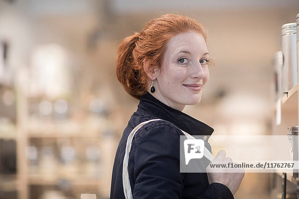 Portrait of red haired woman looking at camera