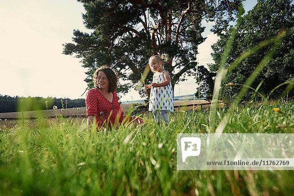 Schwangere Frau sitzt mit Kleinkind im Grasfeld