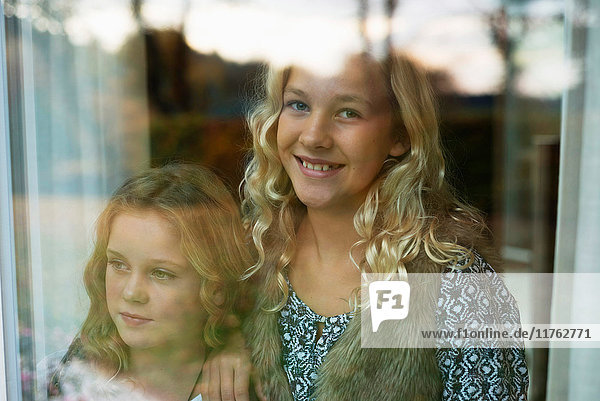 Portrait of two sisters looking through window