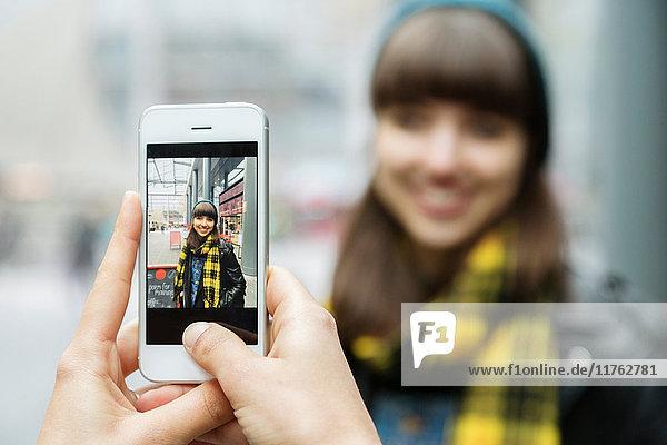 Über-Schulter-Ansicht weiblicher Hände beim Fotografieren der besten Freundin auf einem Smartphone