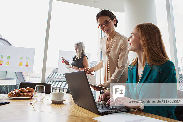 Businesswomen preparing presentation in meeting room