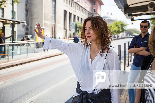 Young woman hailing a bus at city bus stop  Beyazit  Turkey