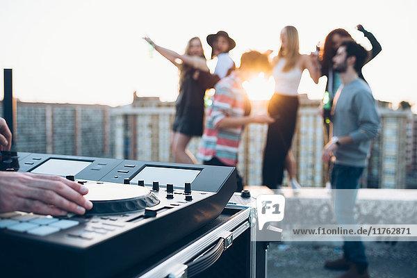 Gruppe von Freunden genießt Dachparty  junger Mann am Mischpult