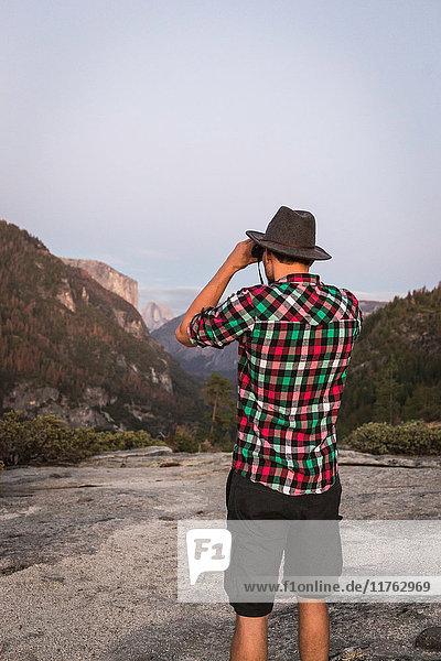 Rear view of man looking through binoculars  Yosemite National Park  California  USA