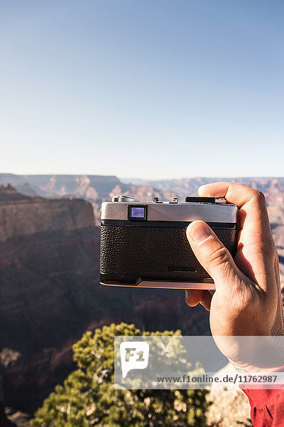 Man's hand holding camera photographing Grand Canyon National Park  Arizona  USA