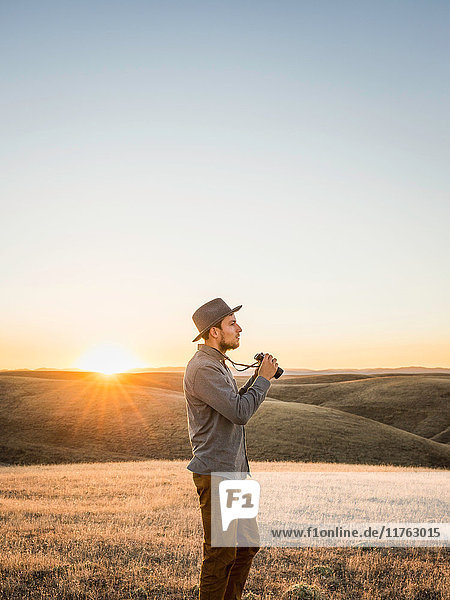 Man with binoculars in rolling prairie hills  Bakersfield  California  USA