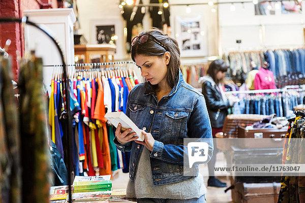 Junge Käuferin betrachtet Buch in Markthalle