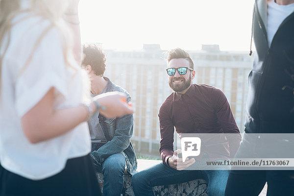 Gruppe von Freunden genießt Dachparty  junger Mann hält Smartphone