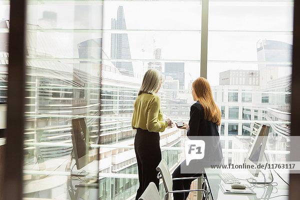 Geschäftsfrauen im Gespräch am Fenster im Büro  London  UK Geschäftsfrauen im Gespräch am Fenster im Büro, London, UK