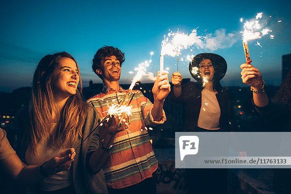 Eine Gruppe von Freunden genießt eine Dachparty und hält brennende Wunderkerzen