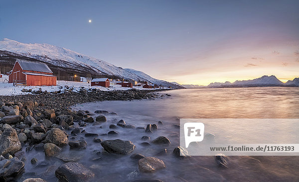 Panorama of typical wood huts called Rorbu framed by fiery sky at sunset and frozen sea  Djupvik  Lyngen Alps  Troms  Norway  Scandinavia  Europe