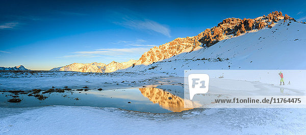 Panorama of Lake  Piz Umbrail at dawn with photographer in action framed by snow  Braulio Valley  Valtellina  Lombardy  Italy  Europe