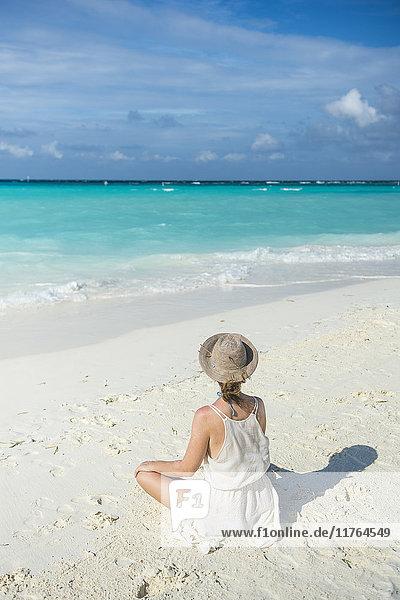Woman sitting on a white sand beach enjoying the turquoise water  Sun Island Resort  Nalaguraidhoo island  Ari atoll  Maldives  Indian Ocean  Asia