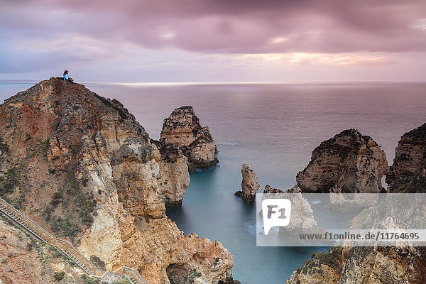 Photographer on top of cliffs surrounded by sea under the pink sky at sunrise  Ponta Da Piedade  Lagos  Algarve  Portugal  Europe