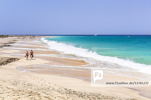 Tourists walking along the sandy beach  Ponta Preta beach  Santa Maria  Sal Island  Cape Verde  Atlantic  Africa