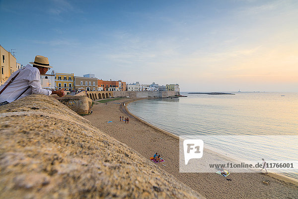 Sunset frames the beach and the turquoise sea  Gallipoli  Province of Lecce  Apulia  Italy  Europe