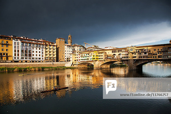 Ponte Vecchio reflected in the Arno River against a dark blue stormy sky  Florence  UNESCO World Heritage Site  Tuscany  Italy  Europe