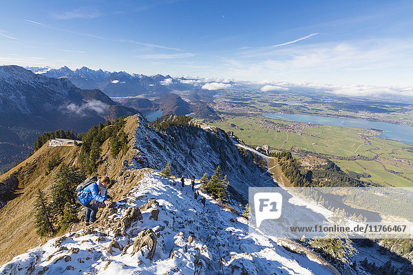 Climbers on steep crest covered with snow in the Ammergau Alps  Tegelberg  Fussen  Bavaria  Germany  Europe