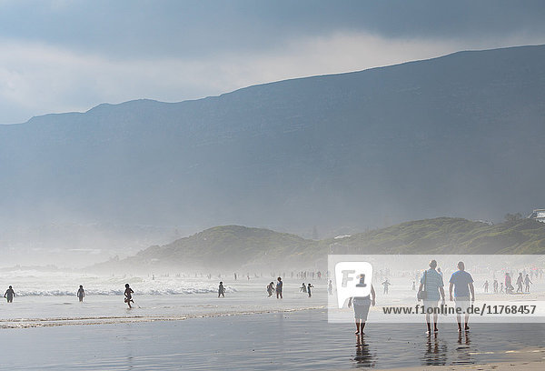 People enjoying walking on the main beach and in the sea in the late afternoon light  Hermanus  South Africa  Africa