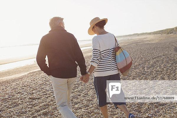 Zärtliches  reifes Paar  das Händchen hält und am sonnigen Strand spazieren geht.