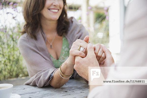 Nahaufnahme eines anhänglichen  reifen Paares  das sich an einem Terrassentisch an den Händen hält.