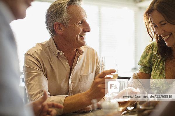 Lächelndes reifes Paar trinkt Wein  speist am Restauranttisch