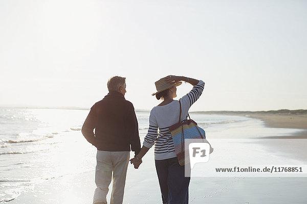 Zärtliches  reifes Paar  das sich an den Händen hält und am sonnigen Strand spazieren geht.