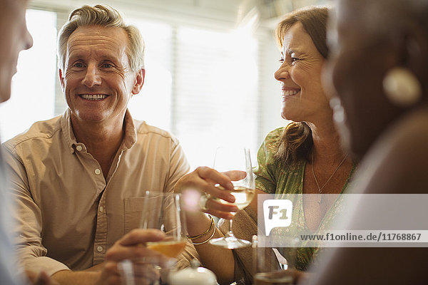 Laughing mature couple drinking wine at restaurant table
