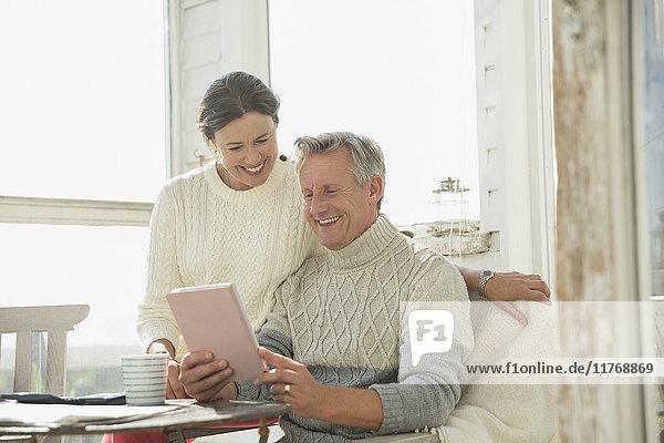 Lächelndes reifes Paar mit digitalem Tablett am Tisch auf der Sonnenterrasse