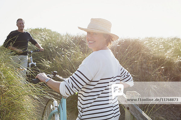 Portrait smiling mature woman walking bicycle on sunny beach grass path