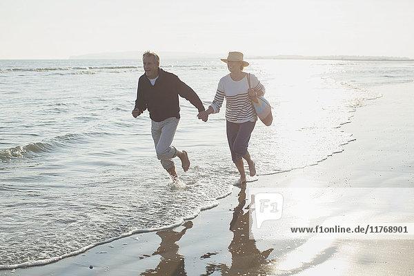 Verspieltes reifes Paar  das sich an den Händen hält und in der sonnigen Meeresbrandung läuft.