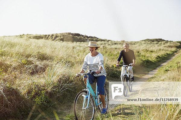Reife Paare beim Fahrradfahren auf dem sonnigen Strandgrasweg