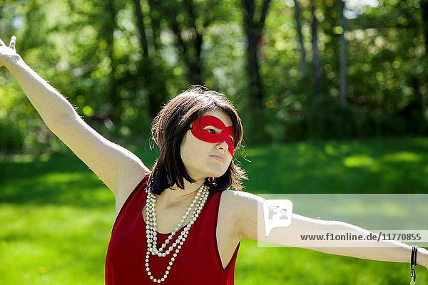 Young woman  with arms outstretched  wearing a mask  pearl necklace  and red dress in a park.