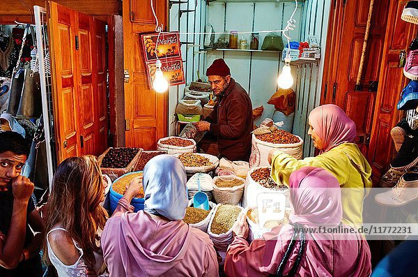 Women gathering in a dried fruit and spices shop in the souk of Fez  Morocco