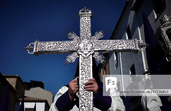 A man holds a silver cross during Easter Week celebrations in Baeza  Jaen Province  Andalusia  Spain.