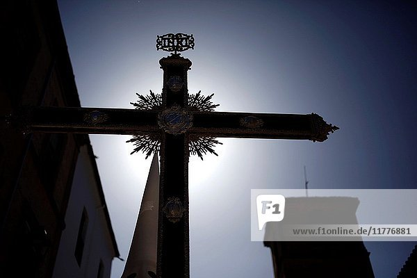 Silhouette of a penitent holding a cross during Easter Week celebrations in Baeza  Jaen Province  Andalusia  Spain.