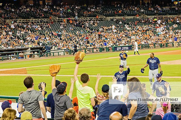 Detroit  Michigan - A baseball player for the Tampa Bay Rays tosses a ball to children in the stands at the end of an inning at Comerica Park  home of the Detroit Tigers.