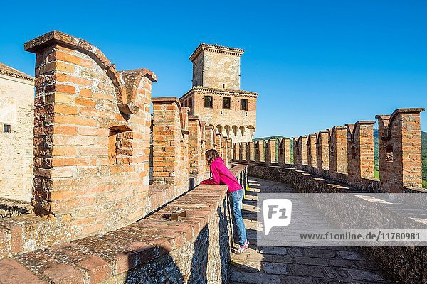 Vigoleno  Piacenza  Emiglia-Romagna  Italy. Woman standing on the castle walls looking the town below.