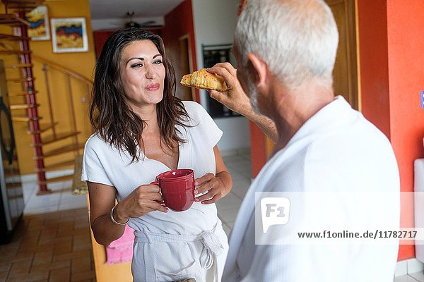 Breakfast of unequal couple - older man feeding a croissant to younger woman  Nuevo Vallarta  Nayarit  Mexico.
