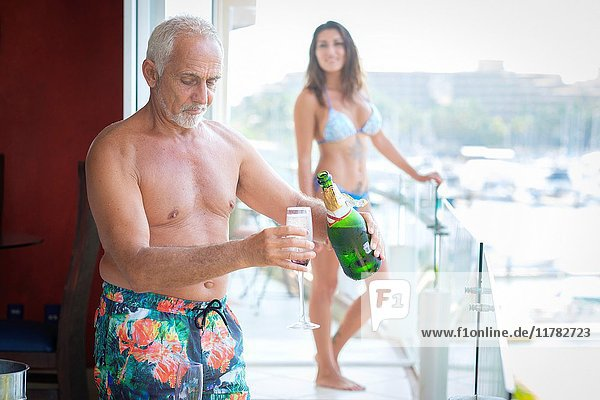 Older caucasian man pouring sparkling wine into glass for younger woman.