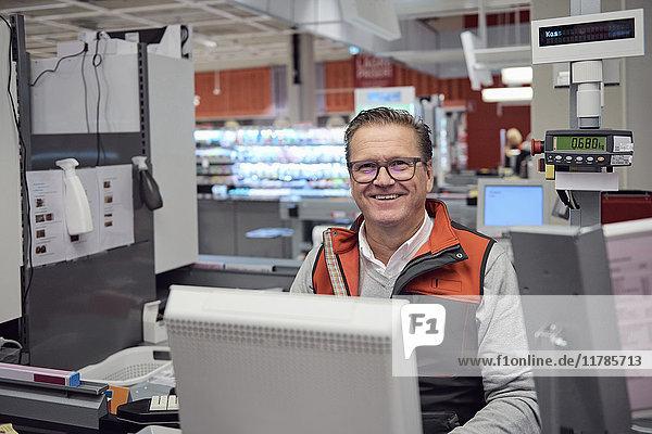 Porträt eines lächelnden reifen Kassierers an der Kasse im Supermarkt