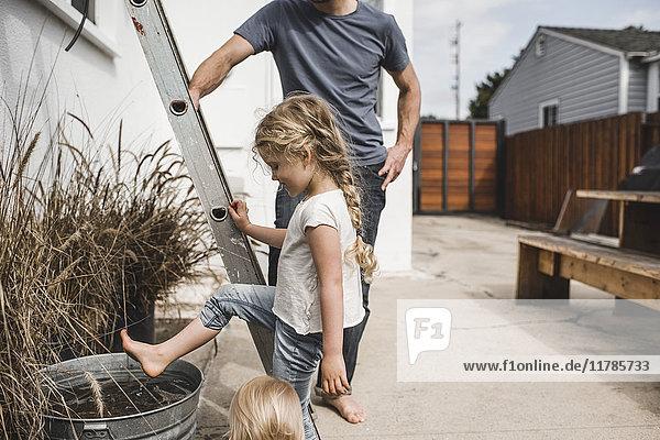 Mädchen spielt mit Wasser im Container  während sie neben Vater und Leiter vor dem Haus steht.