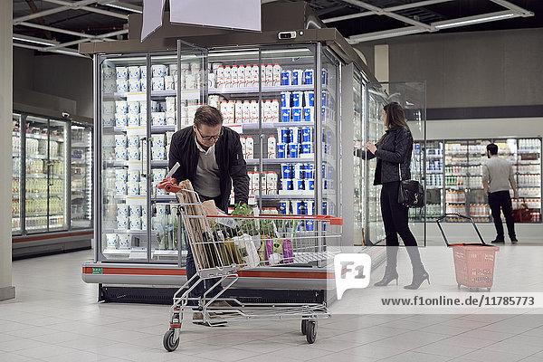 Leute  die Lebensmittel im Kühlregal im Supermarkt kaufen.