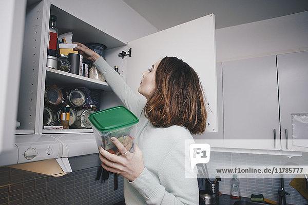 Junge Frau sucht im Küchenschrank