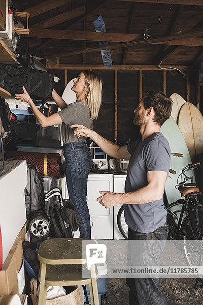 Mittleres erwachsenes Paar  das eine Tasche im Regal im Lagerraum anordnet.